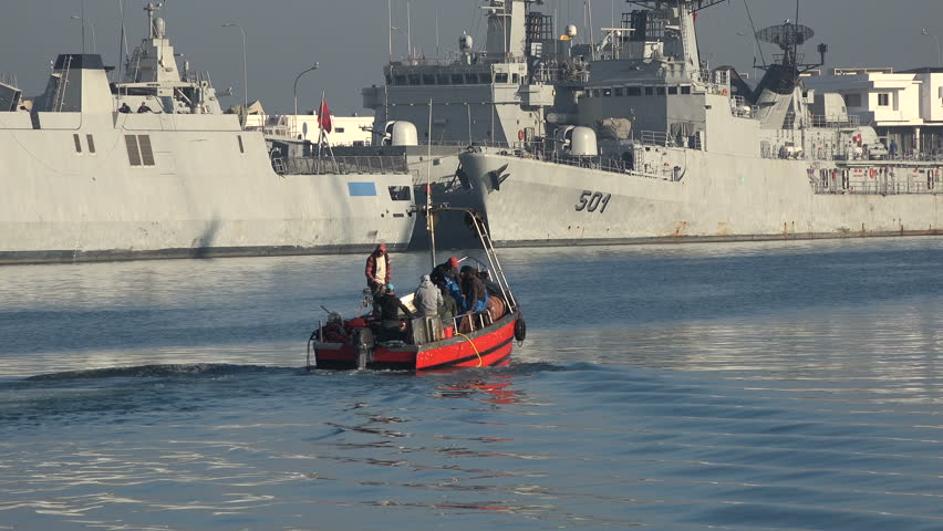 CASABLANCA, MOROCCO - DECEMBER 2016: A small fishing boat sails towards the Atlantic Ocean, with navy vessels in the background, in Casablanca, Morocco