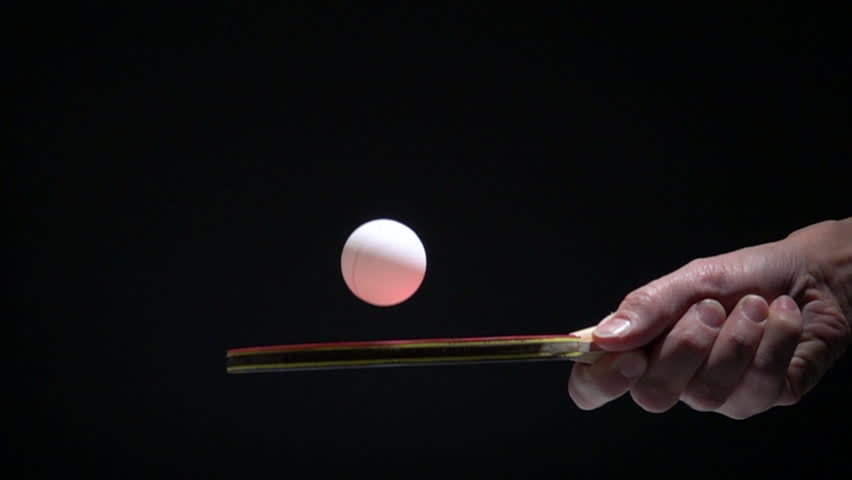 Hand holding table tennis racket and bouncing ping pong ball. Slow motion film clip with sport equipment.