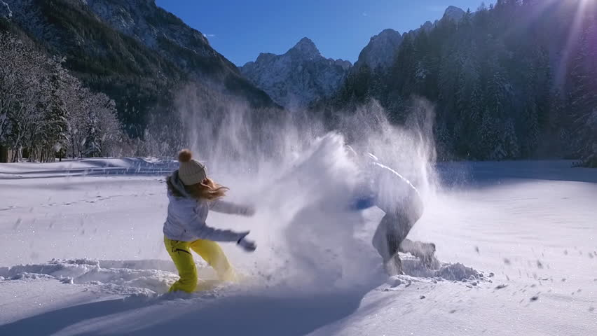 Slow motion - Man grabbing and tossing woman into the snow during a snowball fight
