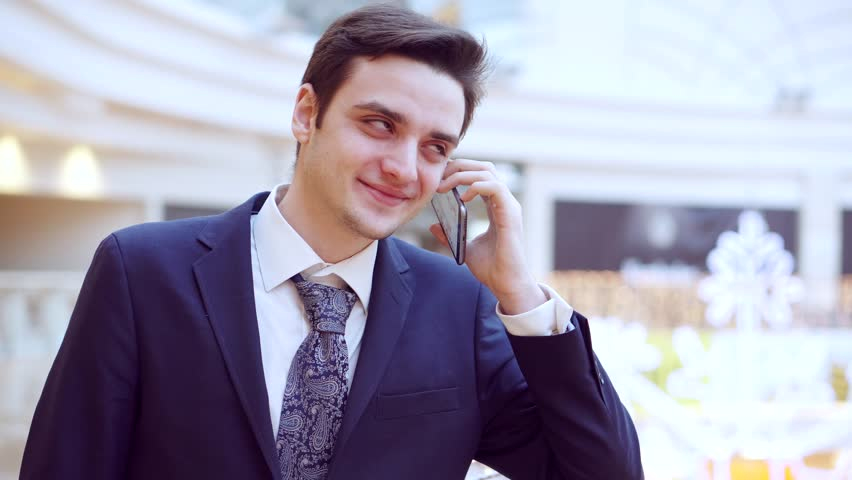 Smart phone man calling on mobile phone. Handsome young business man talking on smartphone smiling happy wearing suit jacket . | Shutterstock HD Video #23130946