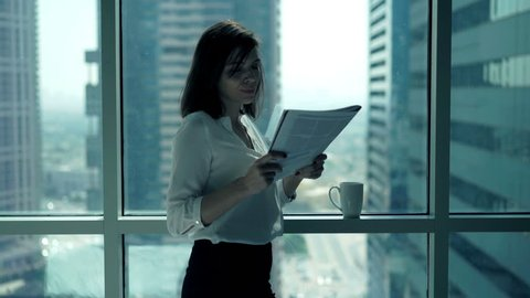 Young businesswoman reading newspaper standing by window in office