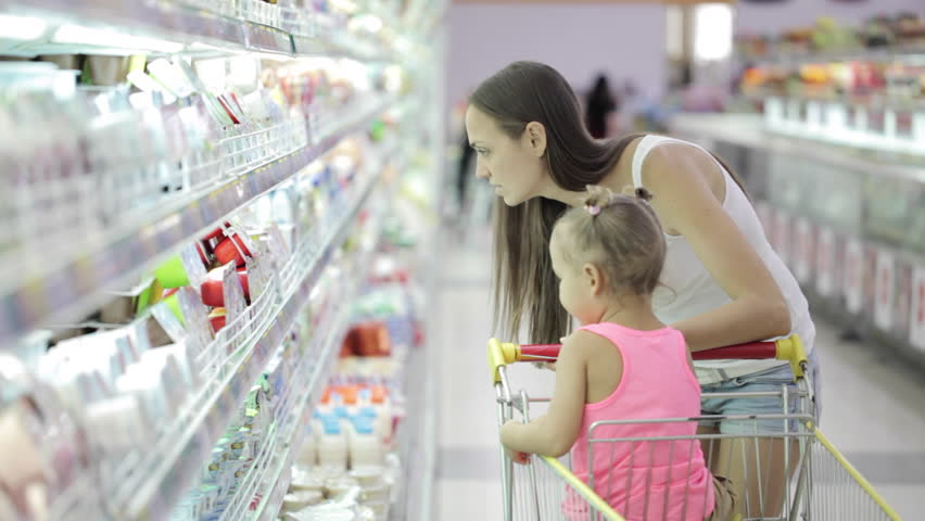 Young attractive woman with cute daughter in shopping cart choosing a yogurt in grocery section at supermarket | Shutterstock HD Video #23156392