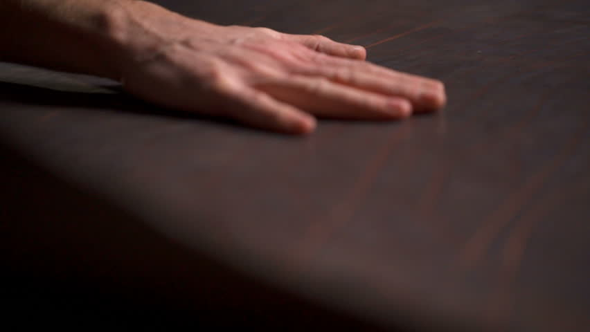 A craftsman sleeking a big piece of leather on the table slow motion