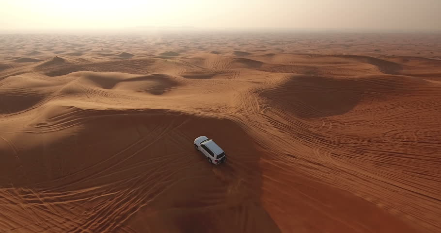 Aerial view of 4x4 off road land vehicle taking tourists on desert dune bashing safari in Dubai, UAE #23180152