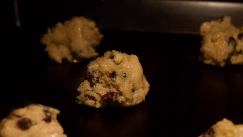 Homemade chocolate chip and raisins cookies - time lapse video. Raw dough melting in oven and changing color to golden brown