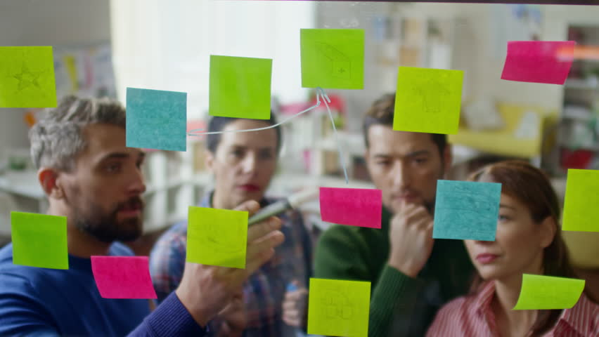 High angle shot of startup workers looking at glass wall planner with post-it notes and linking ideas on them by drawing arrows | Shutterstock HD Video #23184703