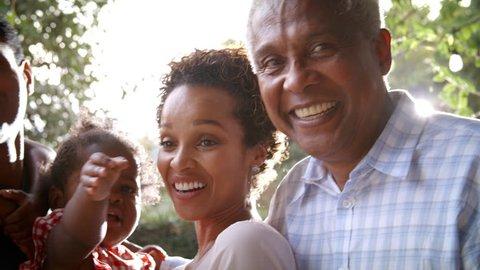 Multi generation black family in garden, handheld pan