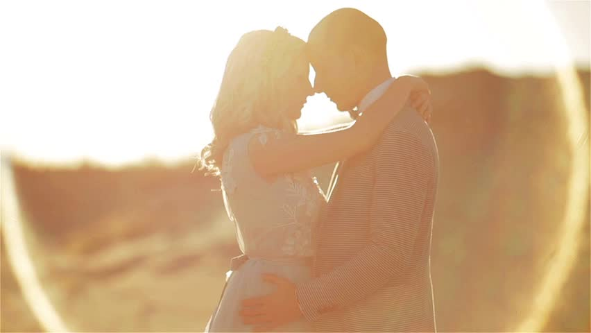 Man and woman pose embracing in morning sand desert closeup of heads and legs. Couple in love stand together in aura of sun holding each other. Togetherness unity honey moon romantic affection concept | Shutterstock HD Video #23232802