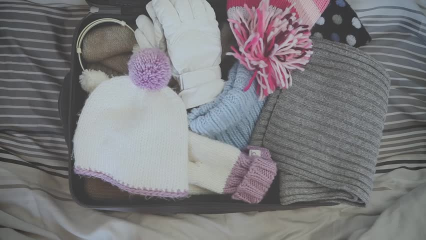 top view of a girl who prepares the suitcase to go to the mountains with hat, earmuffs, gloves, sweater and sunglasses