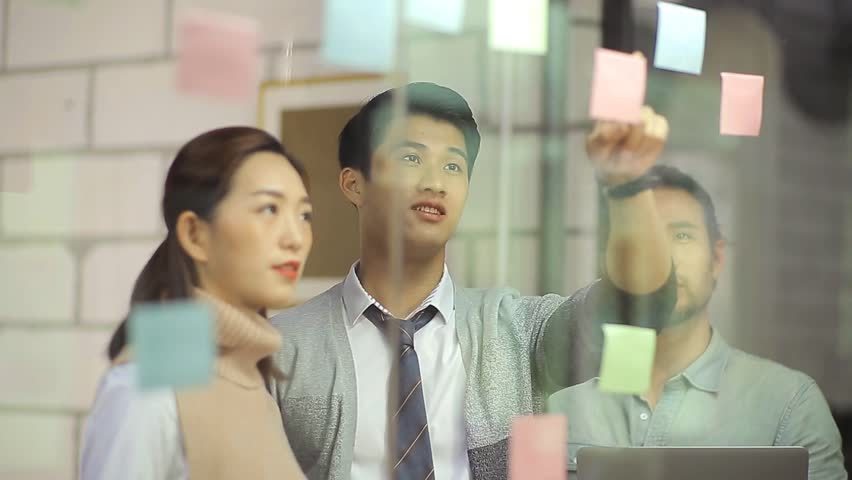 Young asian corporate executives discussing business plan using stickers in office  | Shutterstock HD Video #23248063