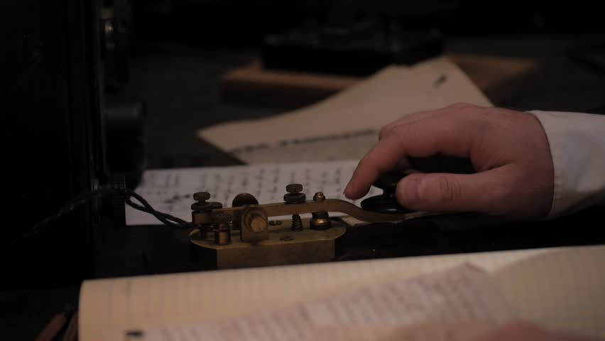 VIRGINIA - SUMMER 2016 - Reenactment, Recreation, historical old telegraph operator with radio machinery and using morse code, taps a message.  Listens to message.  Circa 1890-1920s.  Titanic wireless