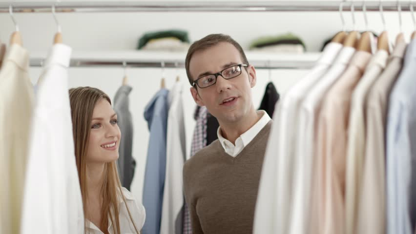 Male customer speaking to sales manager in fashion store while shopping for clothes. Man buying shirt in shop and talking to young woman, girl working as sales assistant, representative
