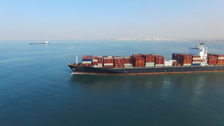 Circa, Circa, January 18, 2017: Aerial footage a large container ship leaving a commercial port, heading for it's next destination port. | Shutterstock HD Video #23280997