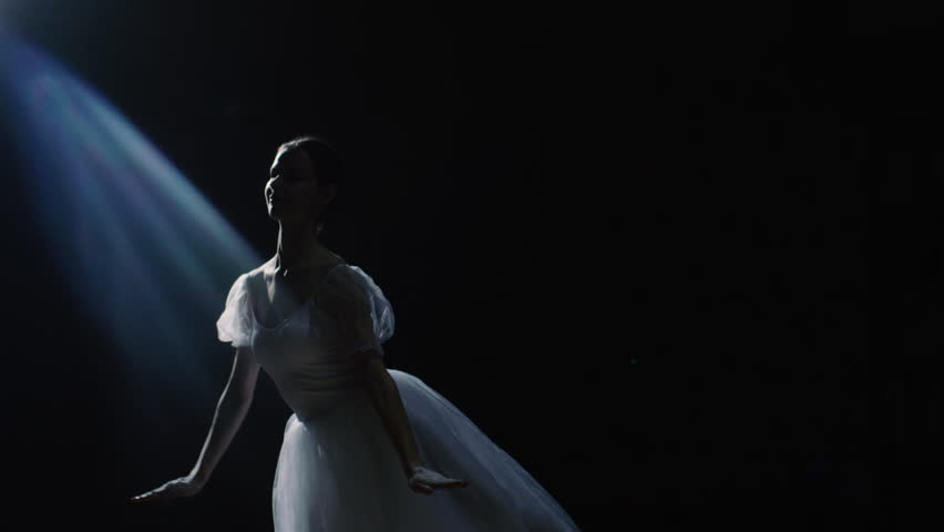 Mid Shot of a Beautiful Young Ballerina Spinning Gracefully in the Spotlight. She Throws Dust Particles in the Air They Shine in the Darkness Around Her. Shot on RED EPIC-W 8K Helium Cinema Camera.
