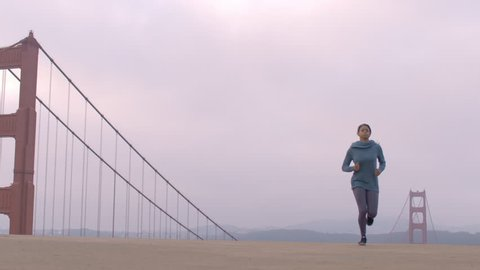 Active woman runs into view from the distance and past the camera with the Golden Gate bridge in the background