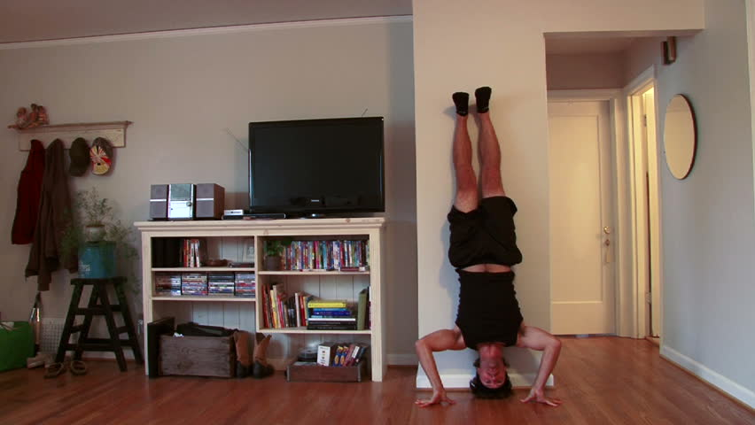 Funny clip of man doing upside down pushups in house.