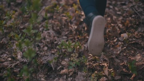 Small teenage girl with long brunette hair and stylish look. Scared little girl running in the forest, she looks around terrified as something is following her, falls down, rushes to get up and run.