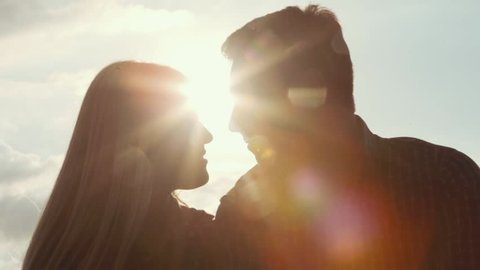 Few shots of young couple darken silhouette kissing and smiling on a bright sunlight. Love story. Being happy together. Happy moments. Outside shooting, sun lens.