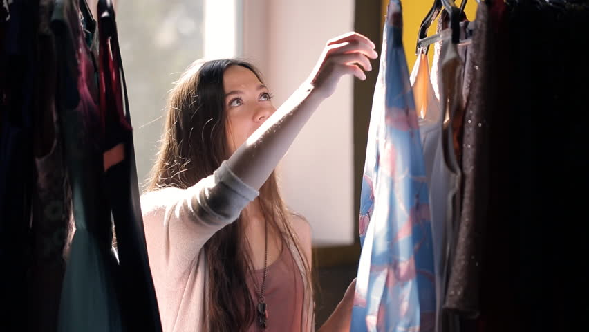 Brown-haired woman choosing dress from rack with hangers inside room. Attractive lady with long brown straight hair looks to dresses, decides what to wear, moves blue attire, takes pink, smiles, goes