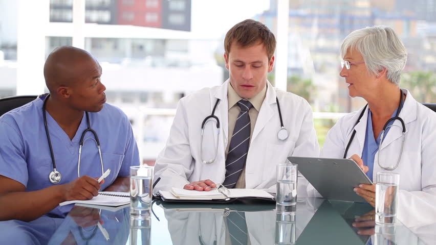 Medical team talking to each other in a bright office