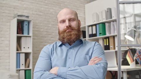 Businessman with red beard sitting with crossed arms in office chair and nodding his head while listening to somebody during video call