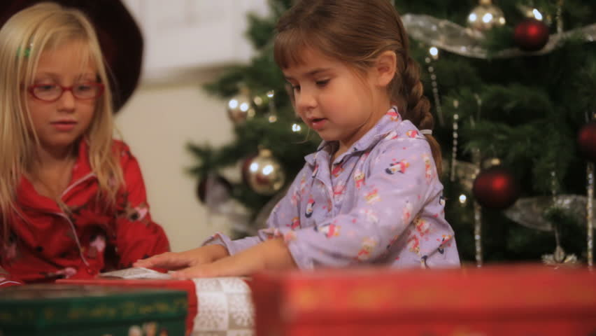 Two little girls opening gifts on Christmas day
