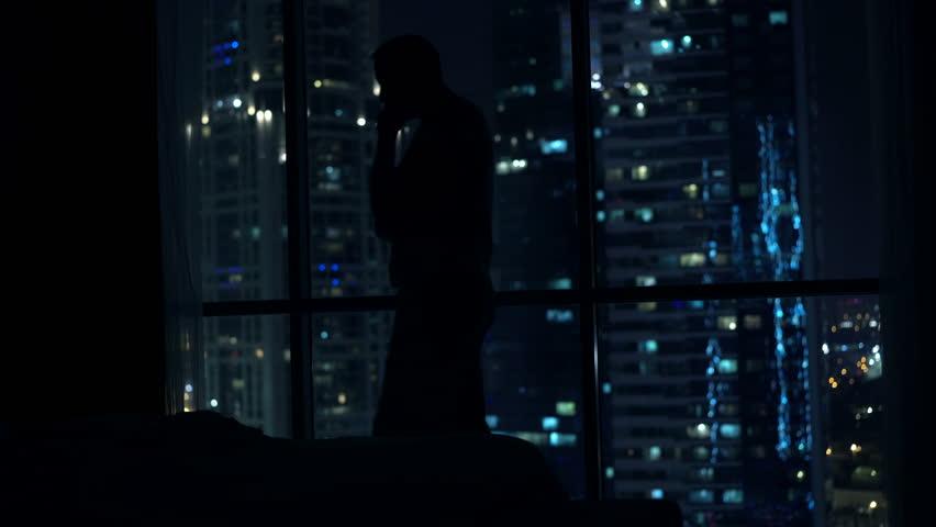 Silhouette of pensive man walking in bedroom by window at home  | Shutterstock HD Video #23437522
