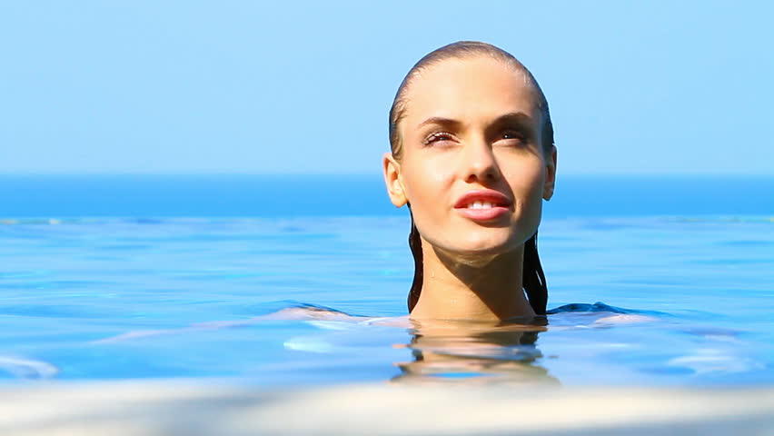 Charming woman reposing in exotic swimming pool
