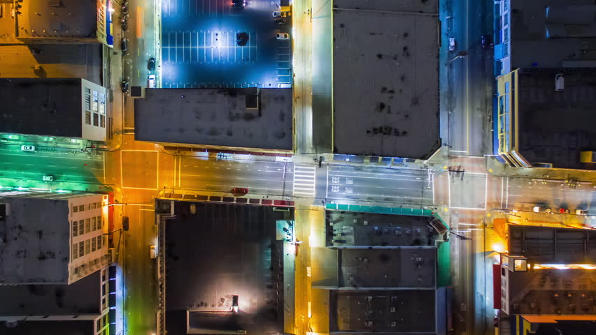 Top down aerial timelapse view of traffic on illuminated street intersections and city blocks in Downtown, Los Angeles. Camera is flying up and rotating. Kaleidoscopic effect