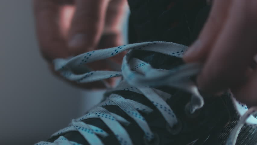 EXTREME CU Caucasian ice hockey player tightening laces on his skates in the locker room, preparing for the game. 4K UHD RAW edited footage