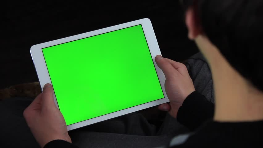 Young man is sitting on the couch and looks at the white tablet. (green screen) | Shutterstock HD Video #23476027