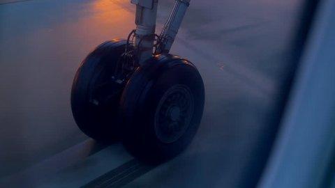 Plane wheel taxiing on airport tarmac at night.