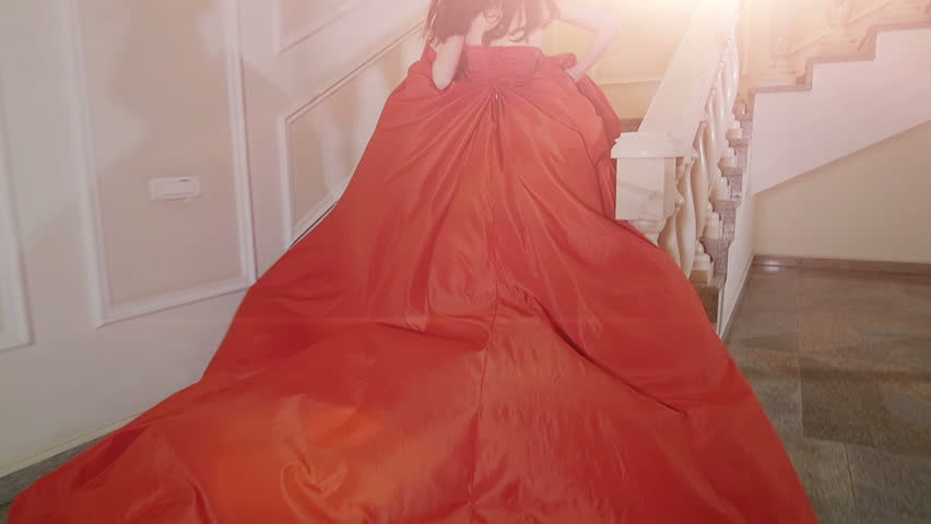 The girl in red dress running up the stairs.