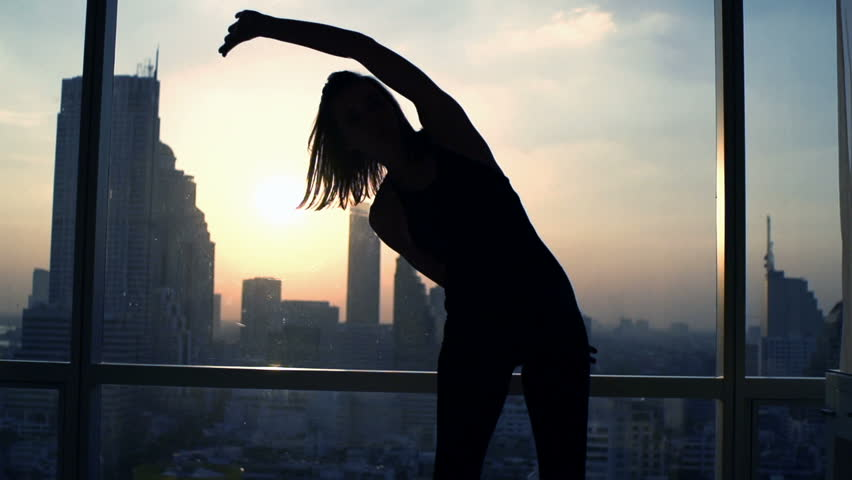 Silhouette of woman exercising bend by window during sunset at home  #23524522