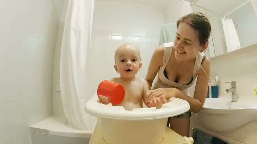 Slow motion of cheerful 1 year old baby boy splashing with mother at  bathtub   HD. 4K Cute Young Brother   Sister In Bathroom  Looking In Mirror