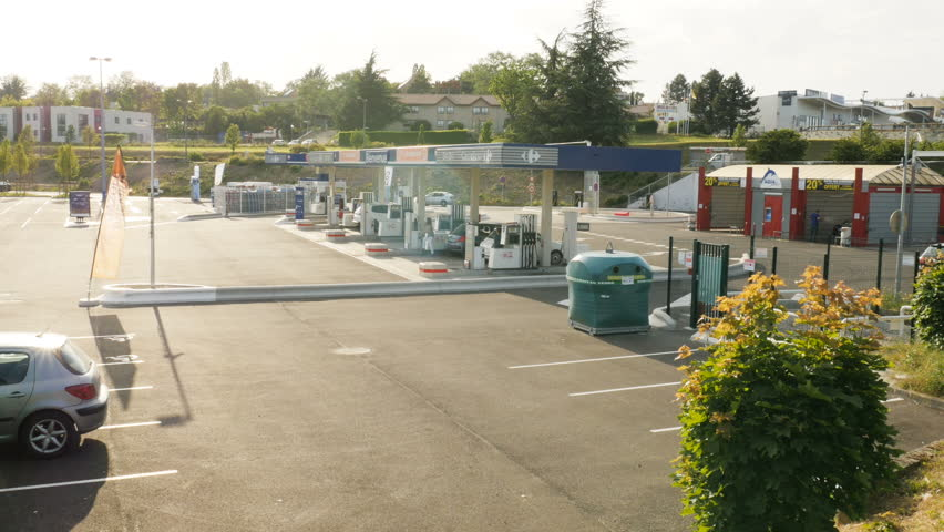 L'Isle-d'Abeau, France - Circa 2017: Carrefour hypermarket supermarket parking with gas station cars filling fuel, diesel gas at the best price - gas station is self-service and operational 24/24.