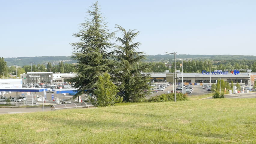 L'Isle-d'Abeau, France - Circa 2017: Large French Carrefour hypermarket supermarket Auchan zone outside town with busy cars driving and people shopping on a warm summer day