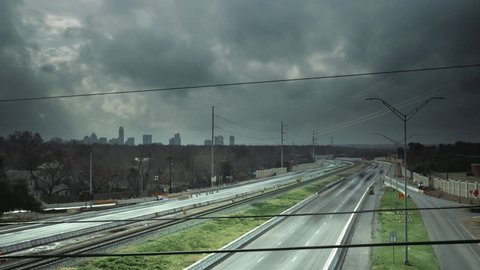 This time-lapse of Mopac Blvd in Austin, Texas features cars, a train, and the city skyline in the background.  Storm clouds are rolling through city proper.