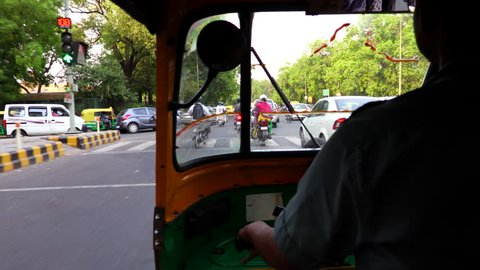 Busy streets of New Delhi, India as seen through an auto rickshaw.