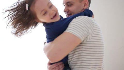 Young Father Hold In Arms Hug And Spin With Little Child Daughter By Bright Window At Home