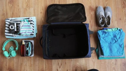tourism, people, luggage and clothing concept - hands packing travel bag with personal stuff