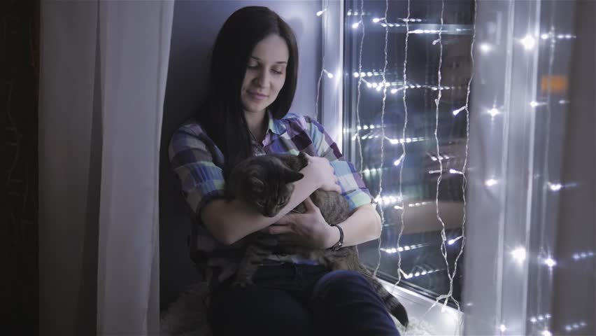 Beautiful Attractive Woman Stroking a Cat Sitting On Windowsill Decorated With Garlands #23643262