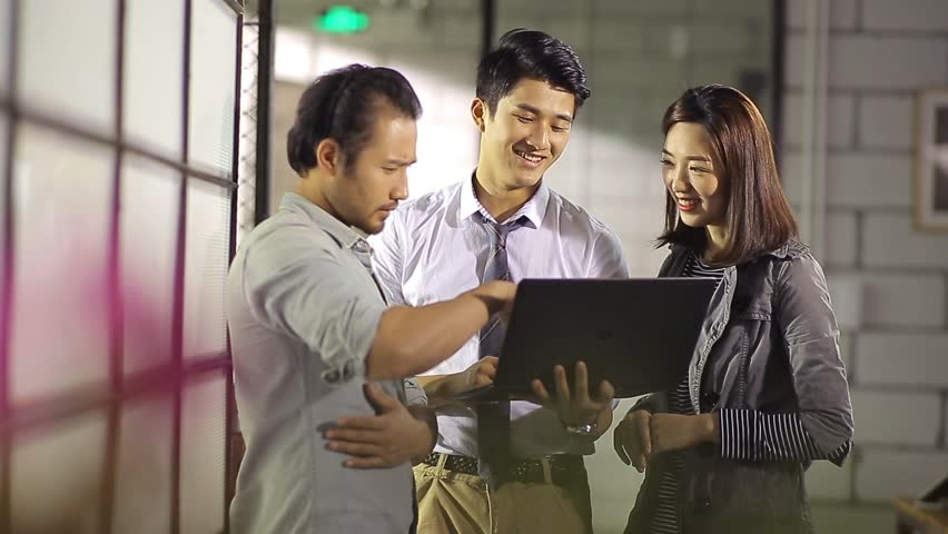 Asian corporate executives discussing business using laptop computer in office.  | Shutterstock HD Video #23645020