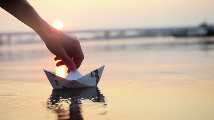 Man's hand putting paper boat on the water and pushing it away during beautiful sunset with reflection sun in the sea in slowmotion, as in childhood.. 1920x1080