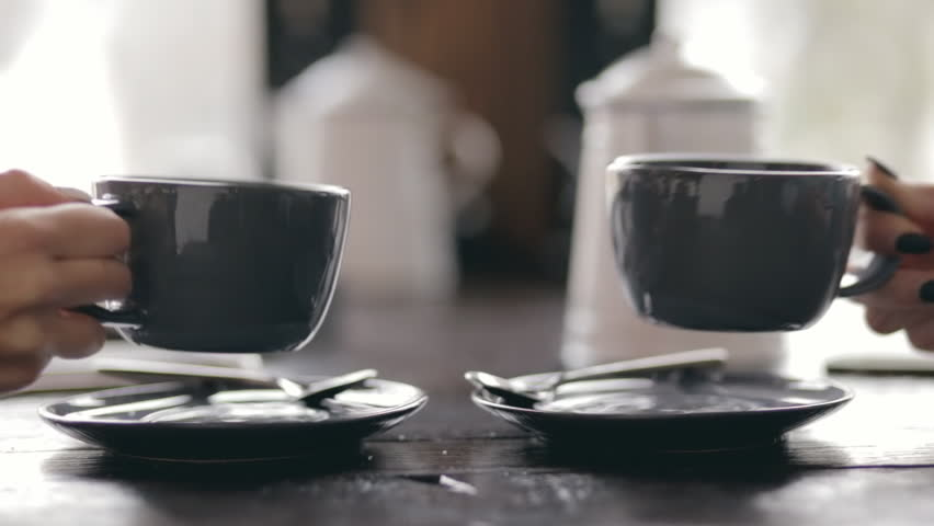 Two women put a cup of tea at same time in cafe - cropped video