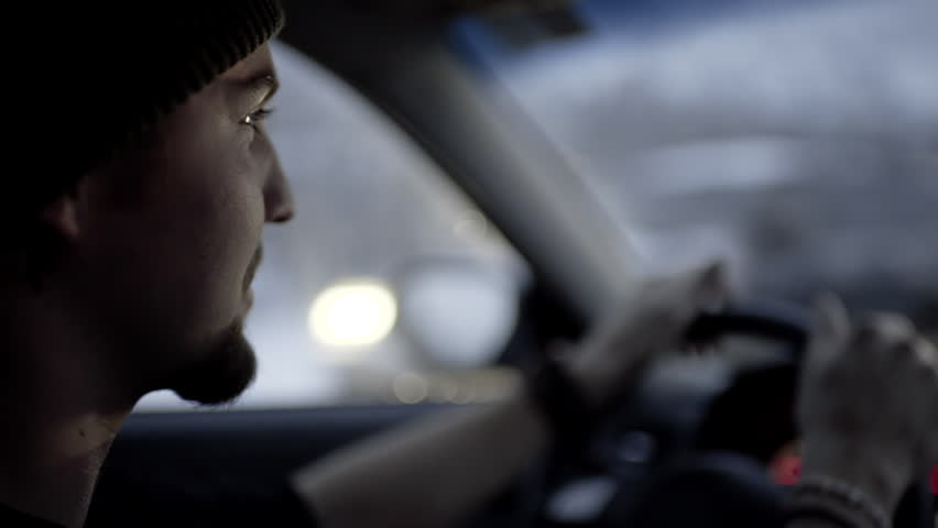Slow Motion Closeup Of Young Man's Face As He Drives On A Snowy Winter Night