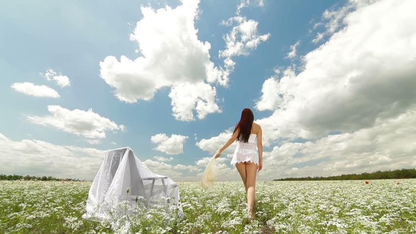 Young Woman Walking Through Summer Field, Rear View