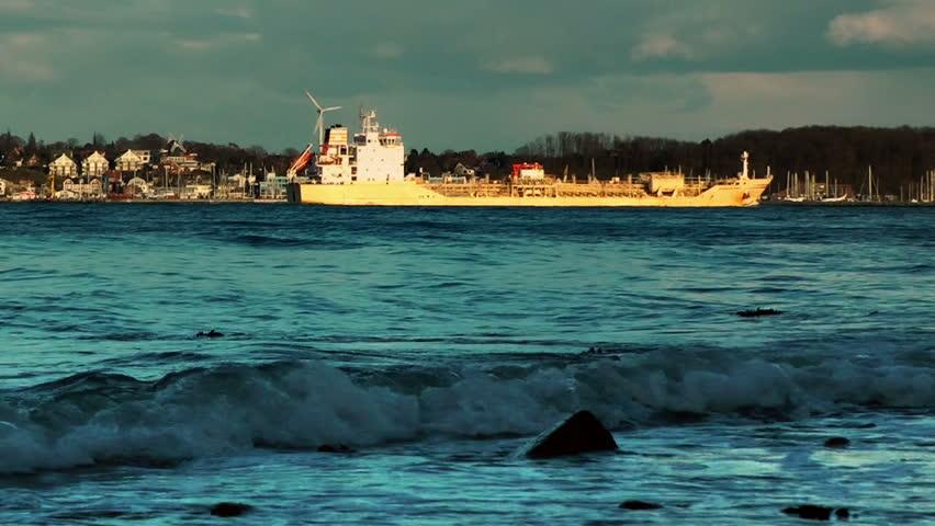 Rolling waves and cargo ship on coastline of Laboe, Kiel, Germany, panning
