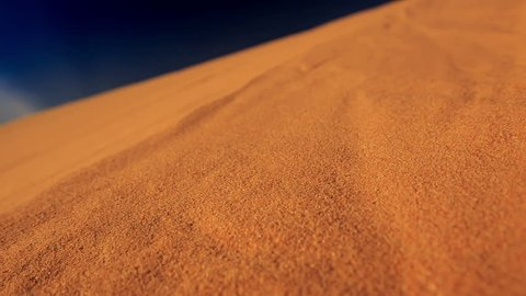 closeup camera moves along yellow quicksand in white sand dunes