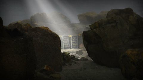 The Ten Commandments situated on the top of Mount Sinai, shrouded in cloud with rays of light illuminating the two tablets. The camera slowly tracks in to view the two stone tablets in detail.